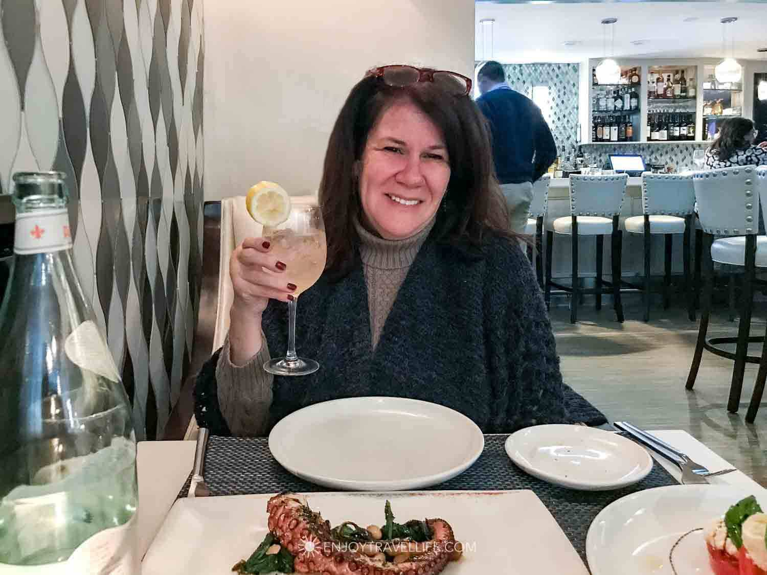 Woman enjoys a drink at il Molo, a seafood restaurant in Boston