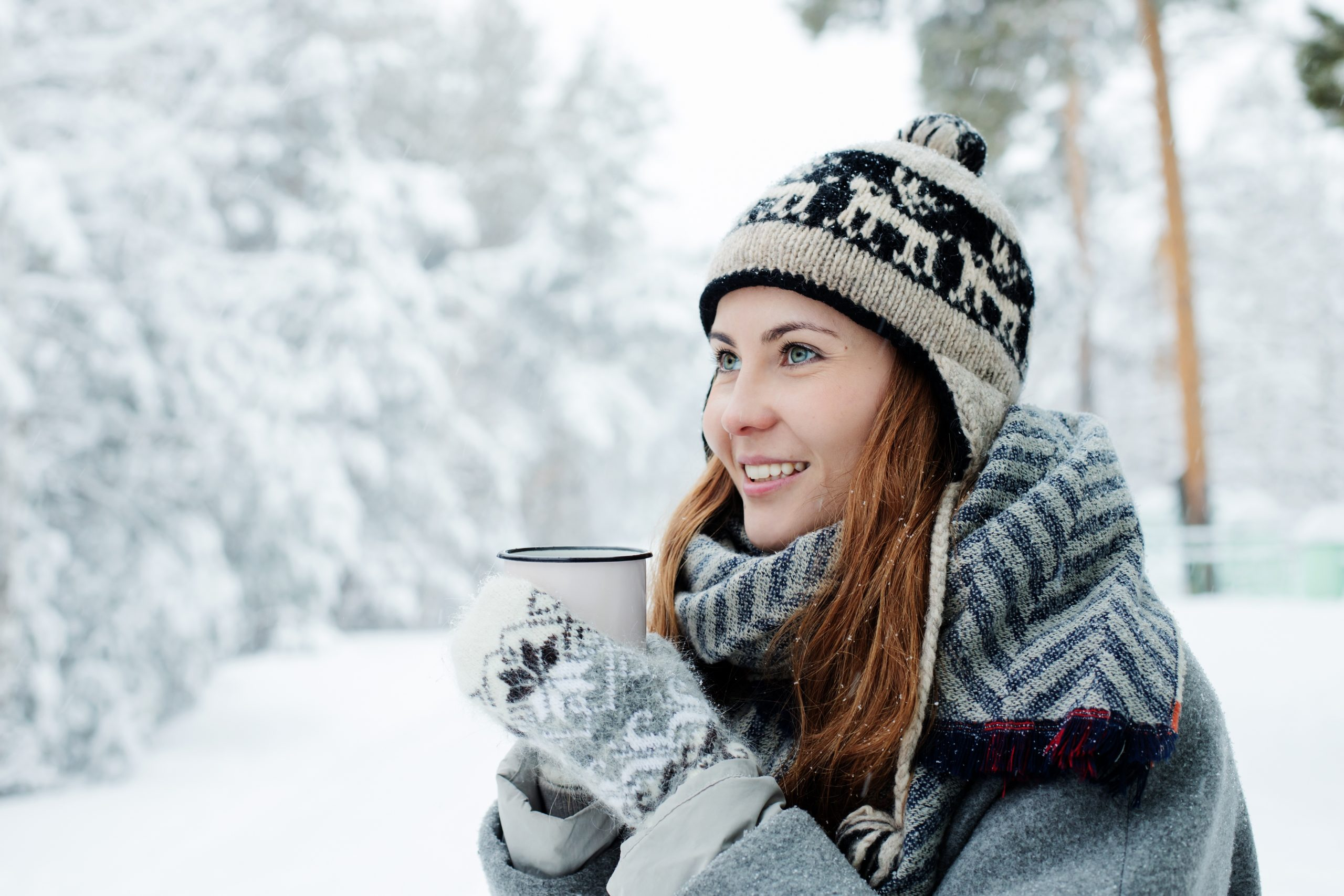 Woman dressed warmly for winter with hot beverage