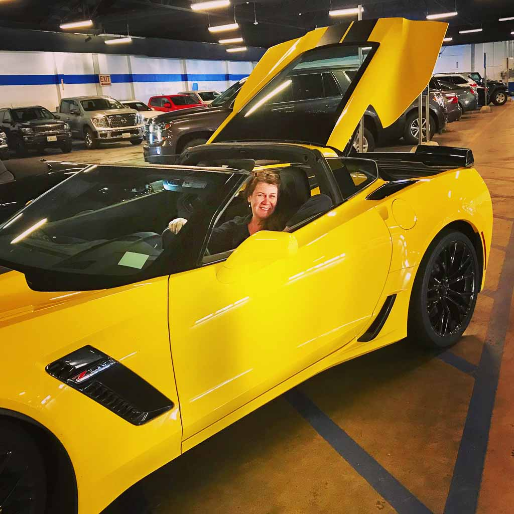 Jackie Gately of Enjoy Travel Life in a yellow sports car