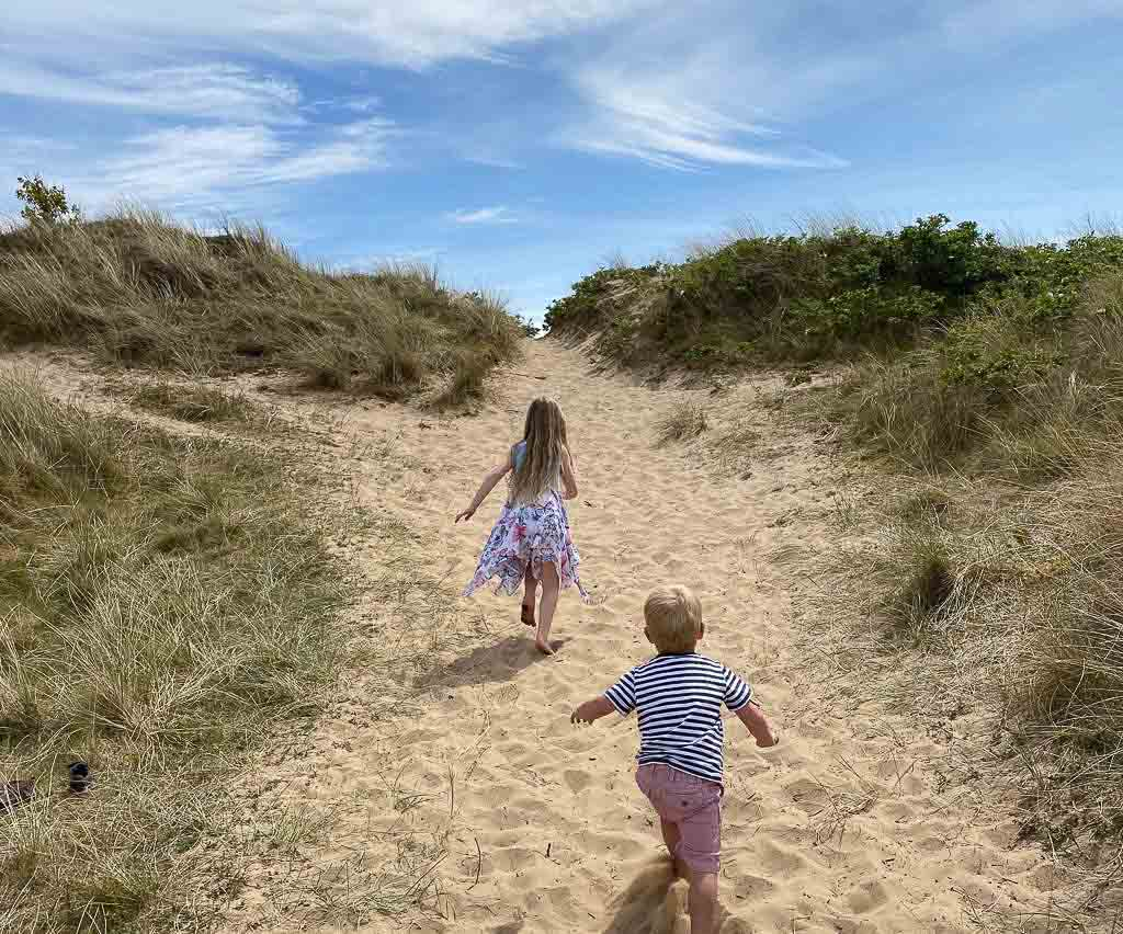 A girl and a boy running up the sandy dune at Formby Beach, The National Trust