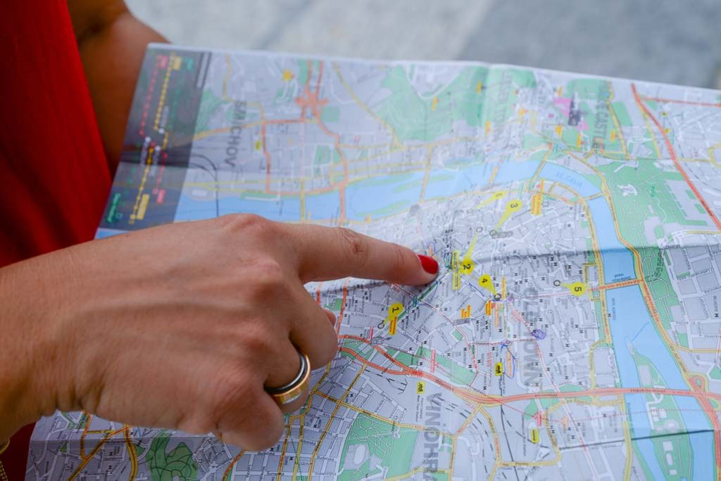 Woman with red fingernail and shirt points to location on a paper |  Driving Radius Map