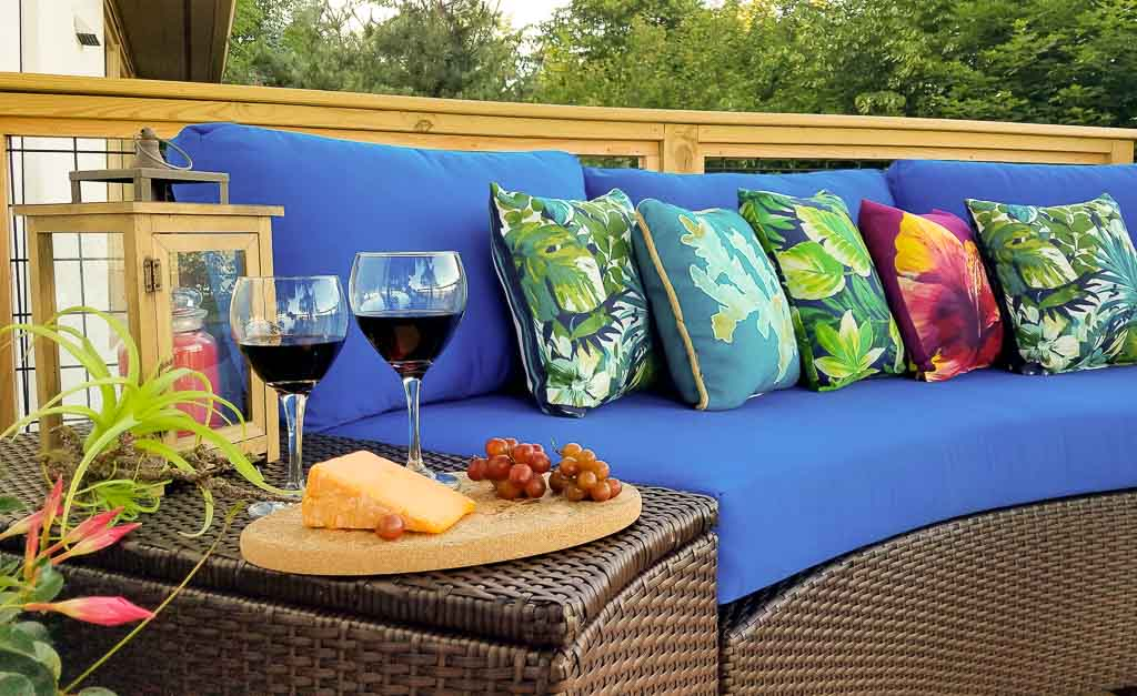 Luxury Outdoor Living Space: Blue outdoor couch with pillows, wine and cheese on side table
