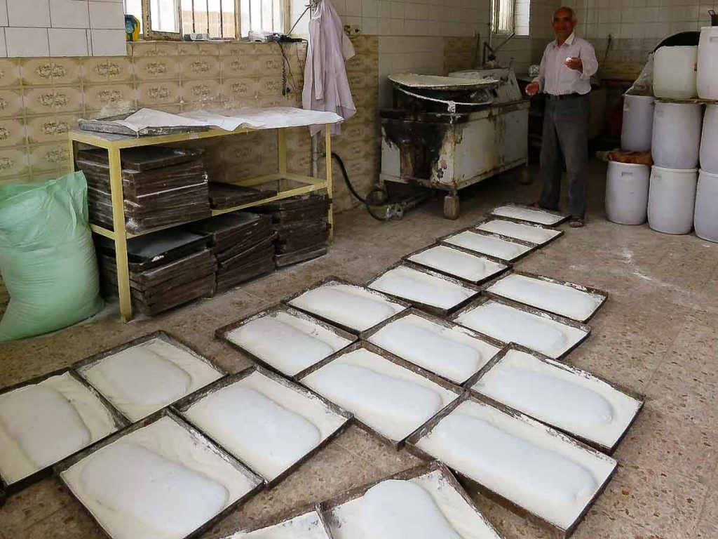 Trays of white Gaz confection are laid out on the floor as the candy-maker looks on. Iran