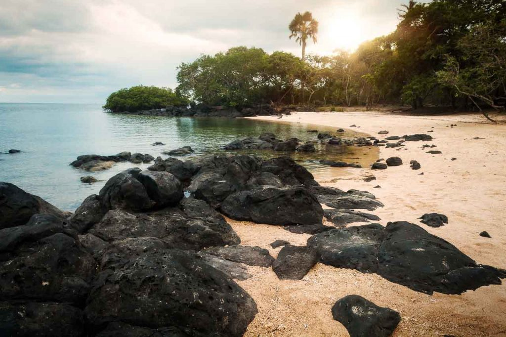 Banda Neira Island, one of the Banda Islands in Indonesia. A view of the beach with black rocks, soft sand, and palm trees.
