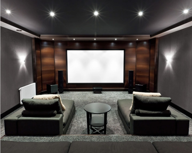 Home movie theatre in the basement with two lounge chairs, a side table, large screen, and a sound system