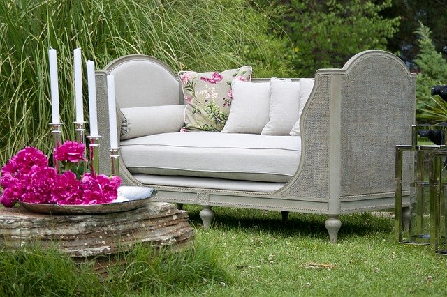 A formal couch on the lawn beside a tray of pink flowers and tapered candles