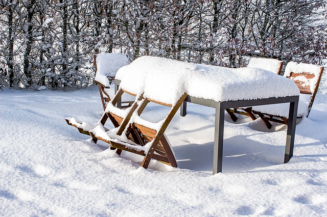 Checklist for Winterizing Your Home: Clean and store outdoor furniture (shown: patio set in snow)