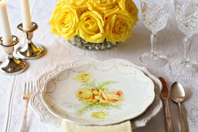 An old-fashioned white place-setting with yellow roses, silverware, white linens, crystal goblets, candles, and yellow roses.