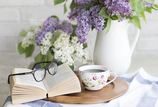 Staycation ideas for singles: book, reading glasses, teacup and lilacs.