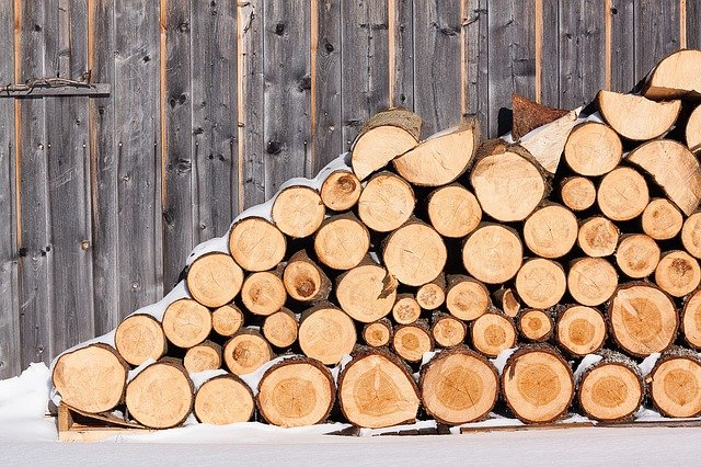 Checklist for Winterizing Your Home: Order and stack wood (shown, stack of wood with a dusting of snow)