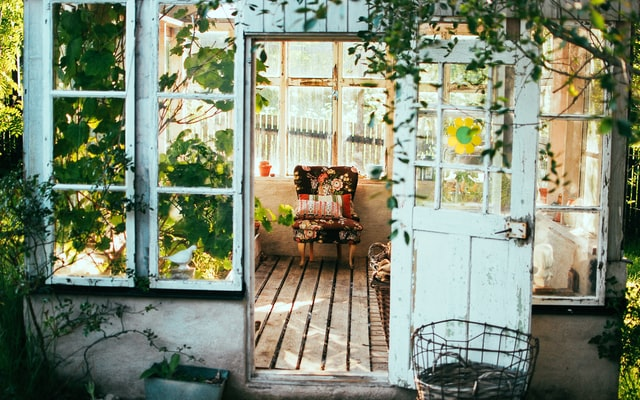how to create more space in your home: a shed with a comfortable chair and shabby chic decor