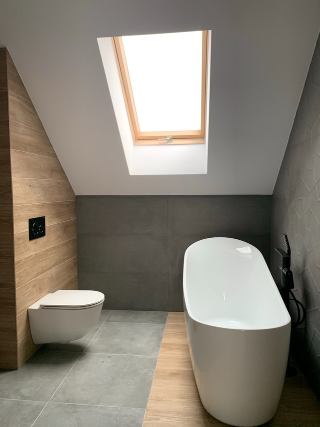 how to create more space in your home: an attic bathroom with soaking tub and skylight