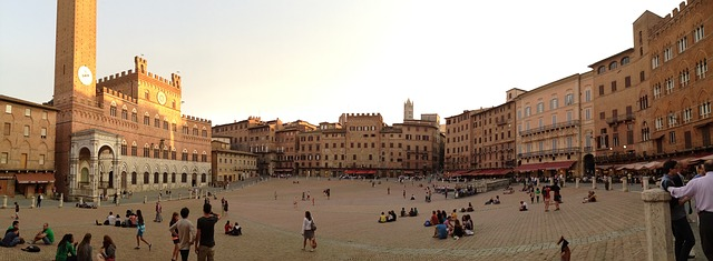 A panoramic view of Piazza del Campo with small groups of people gathering