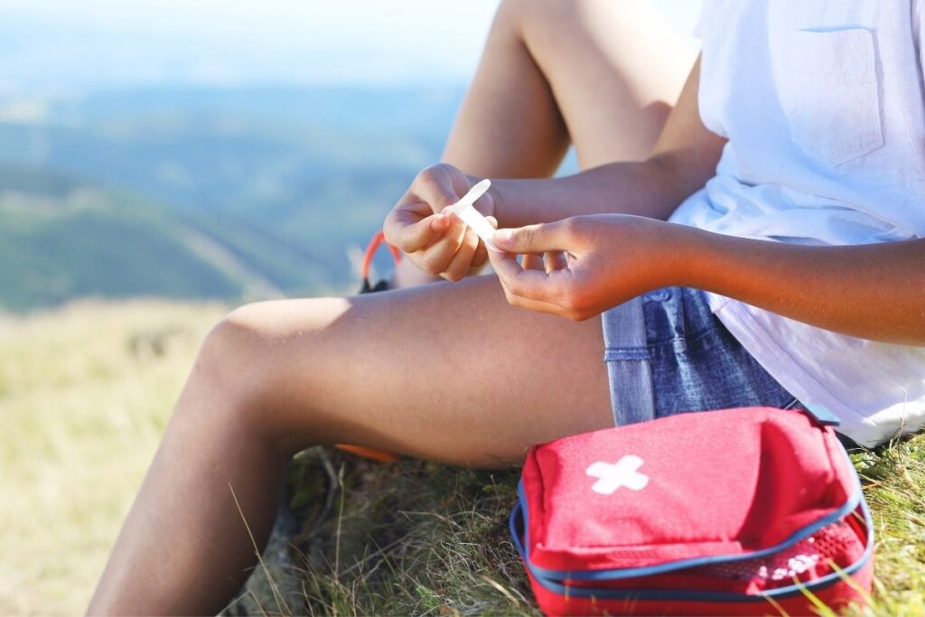 safety tips for summer vacataion - woman with a bandage and first aid kit