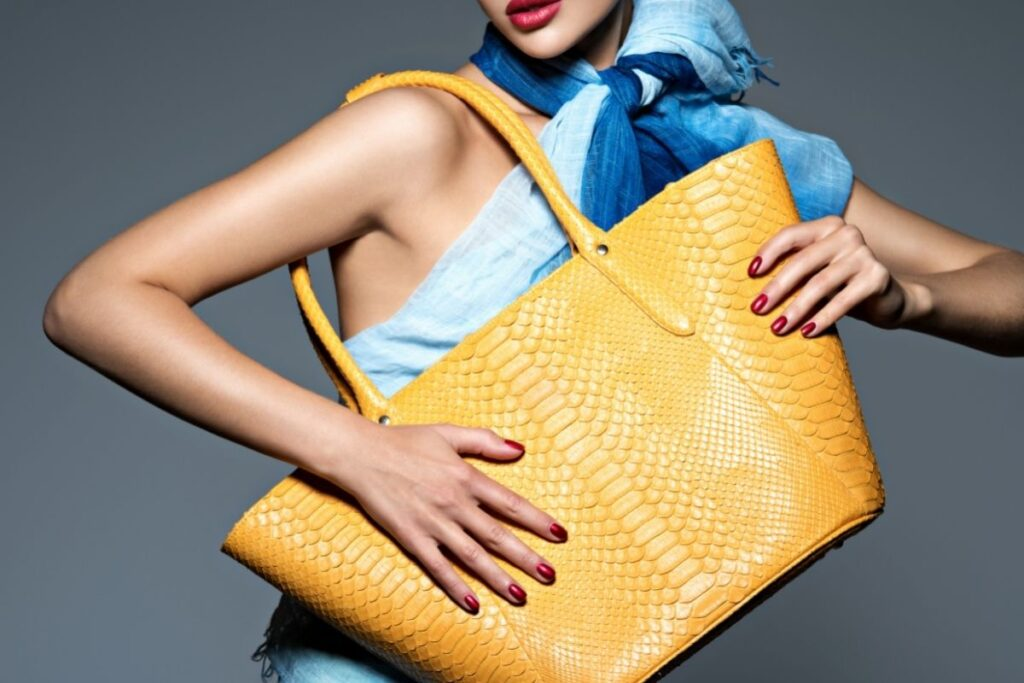woman with yellow alligator purse and blue scarf