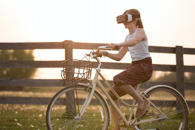 Girl riding bicycle wearing virtual reality glasses