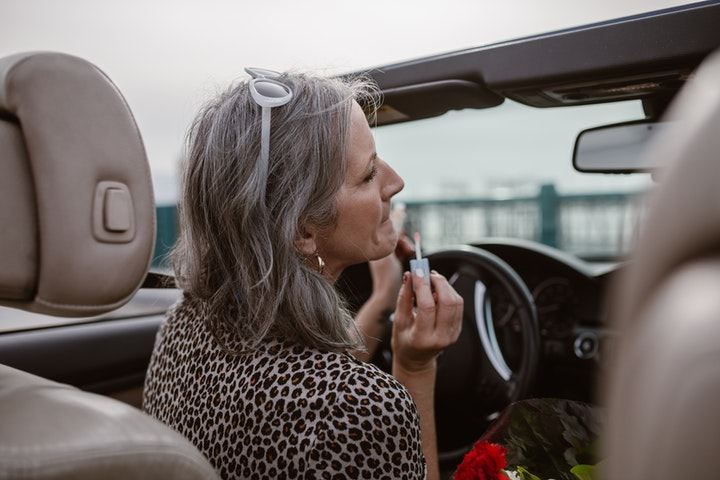 middle-aged woman in car applying lipstick