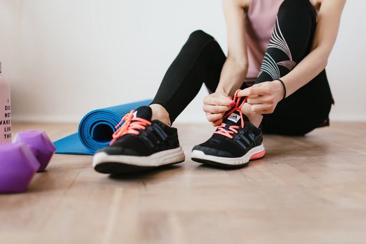 woman lacing up gym shoes